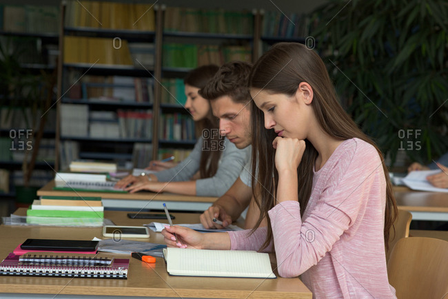 College students studying at desk in classroom