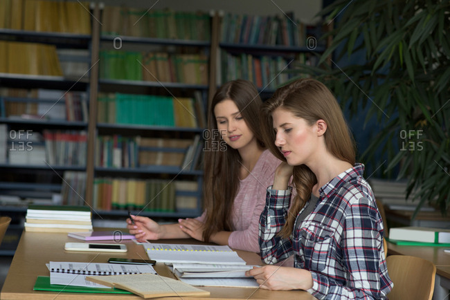 Female college students studying at desk in classroom