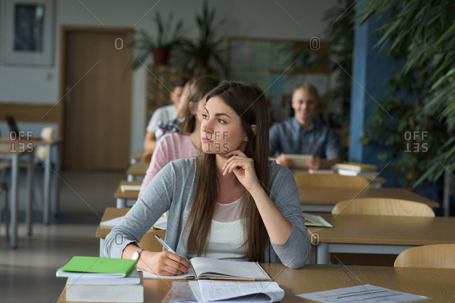 Thoughtful female college student at desk during exam in classroom
