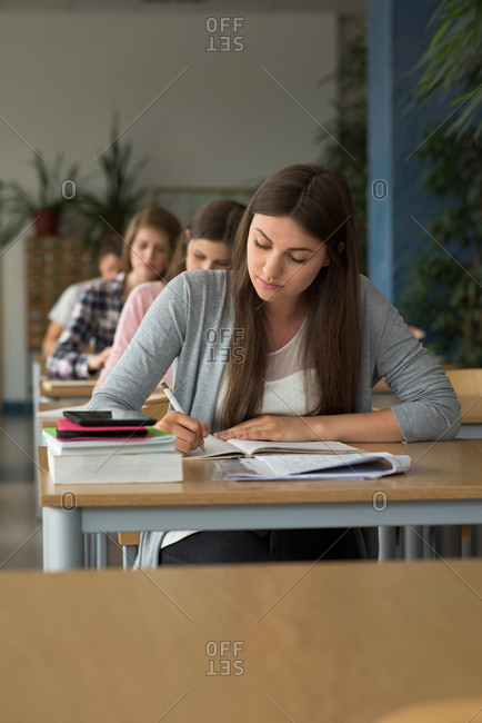 College students writing on book while sitting at desks during exam in classroom
