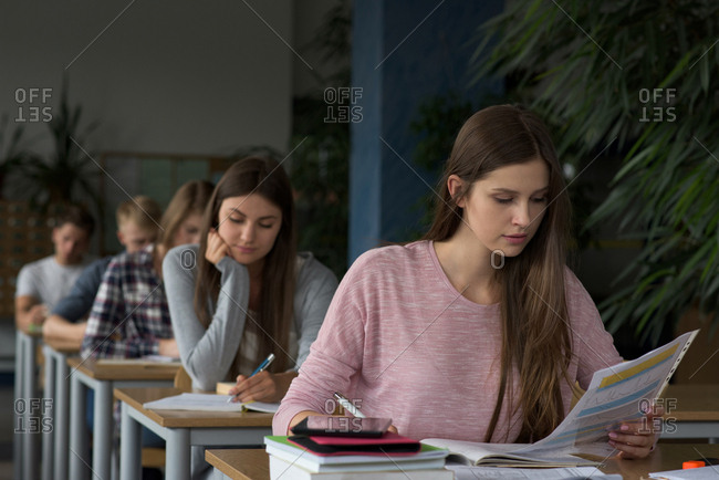 University students sitting at table during exam in classroom