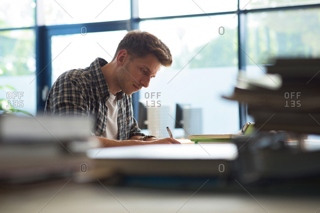 Side view of young male student studying at desk by window in classroom