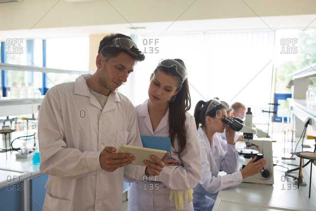 Male student showing tablet computer to friend while standing in lab