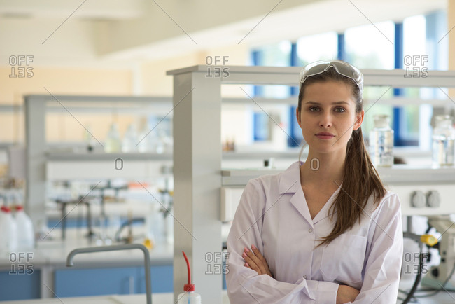 Portrait of female student with arms crossed standing in lab