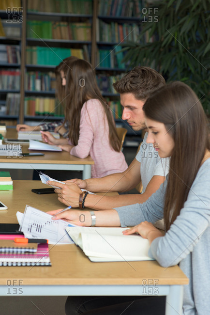 Side view of college students studying at desk in classroom
