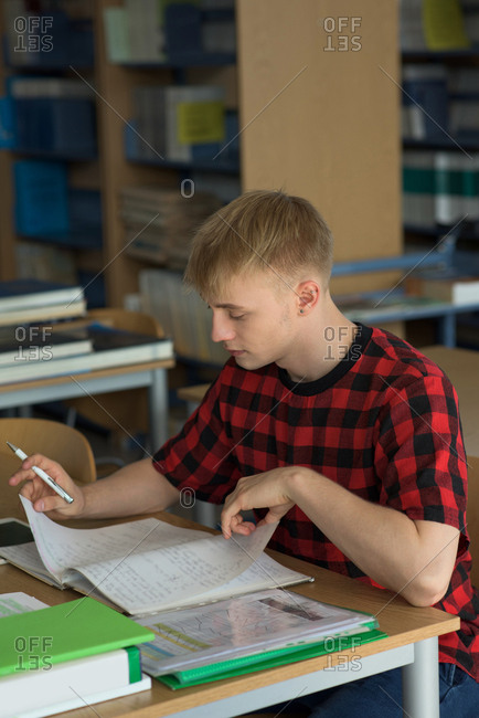 High angle view of young male student studying at desk in classroom