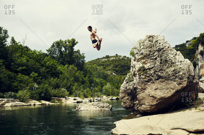 Man leaping from rock into river