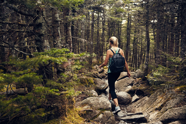 Woman hiking over forest boulders