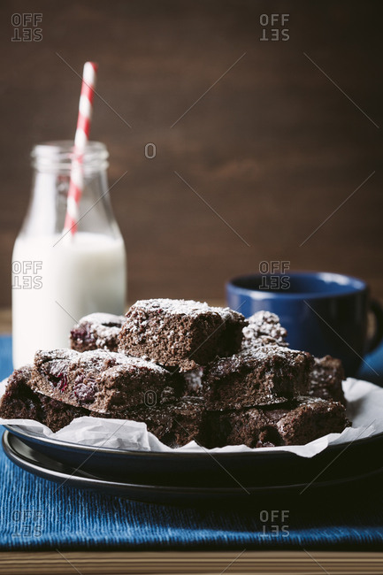 Plate of chocolate cherry brownies with milk