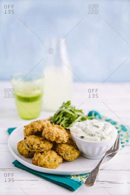 Mini kale and corn cakes with herb yogurt dip