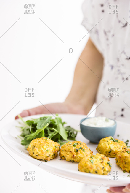 Woman serving kale and corn cakes appetizer