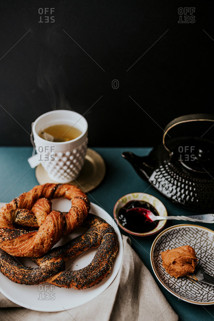 Two pastry pretzels together with peanut butter, blackberry jam and tea in a tea cup, next to black teapot