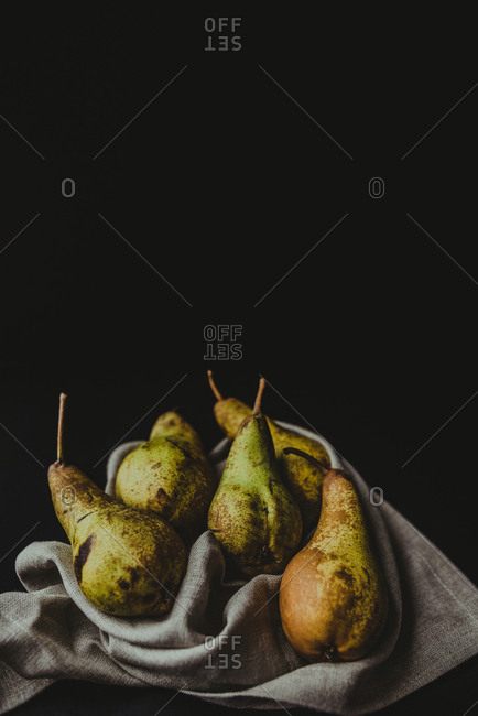 Five pears placed on a cloth on black background simulating still life paintings