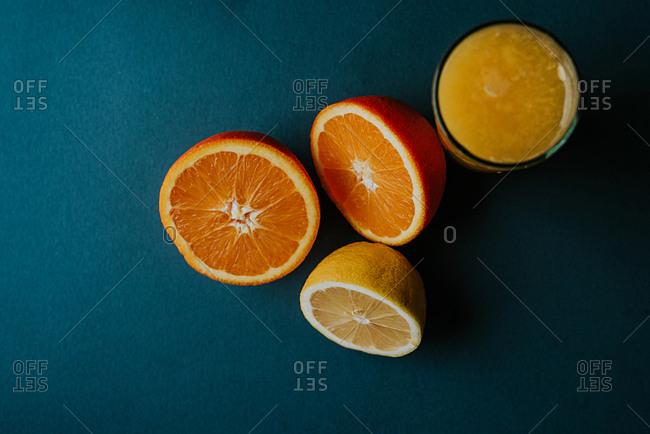 Fresh orange and lemon cut in half together with a glass of fresh orange and  lemon juice on a blue background