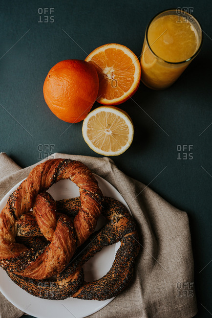 Two pastry pretzels served on white plate next to fresh squeezed orange and lemon juice together with fresh oranges and lemon cut in half being placed beside the glass.