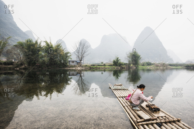 Guilin, China - February 28, 2017: Woman cooking fish over a fire on a raft in Guilin