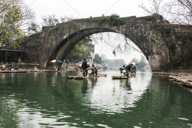 Guilin, China - February 28, 2017: Men transporting passengers on bamboo rafts in Guilin