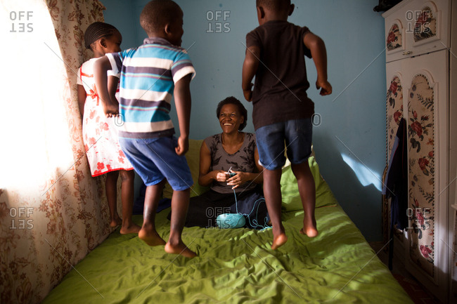Three children jumping on bed whilst mother crochets