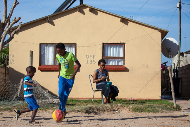 Port Elizabeth, South Africa - February 6, 2017: Children playing with a ball outside whilst mother watches and crochets