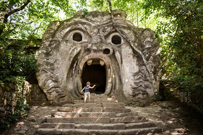 Boy walking into mouth of stone sculpture