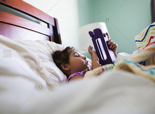 A girl plays with a digital tablet in bed