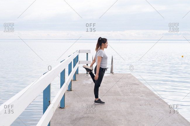 Woman stretching quads on pier