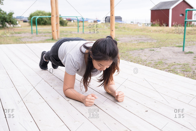 Woman holding plank position on platform in park