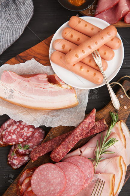 Hot dogs, salami and other cured meats on cutting board