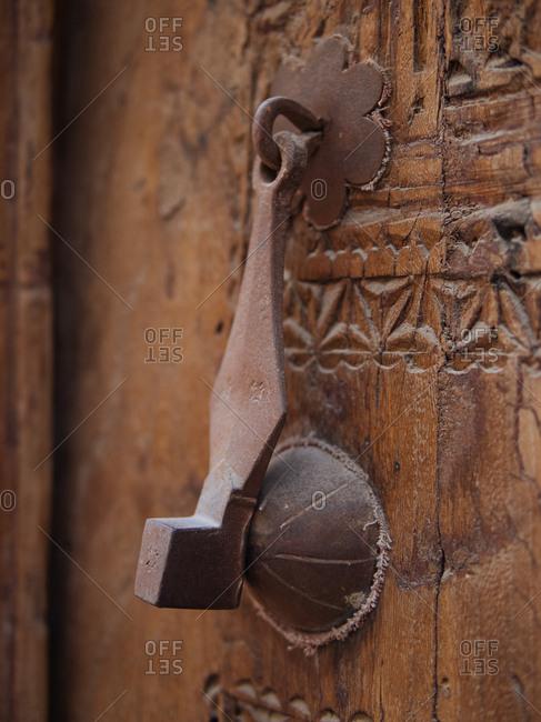 Antique iron door knocker on carved wooden door