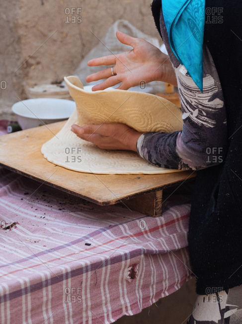 Woman making flatbread outdoors