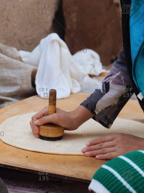 Woman pressing circle of dough with wooden stamper