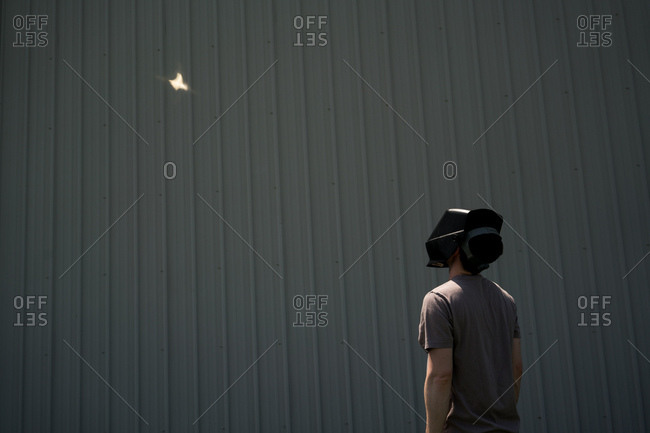 Person wearing welding helmet watching the reflection of the total eclipse near De Soto, Missouri