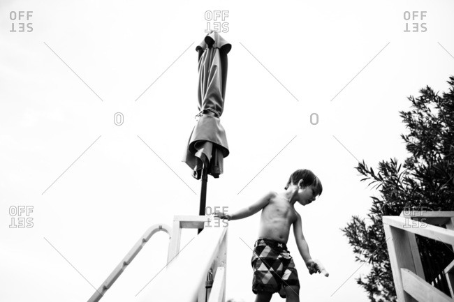 Boy with water gun standing at top of stairs