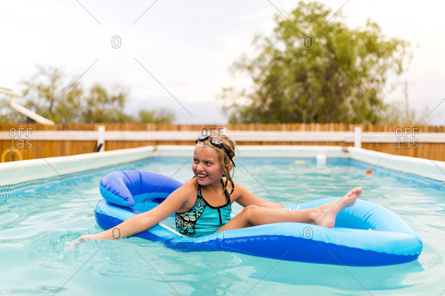 Girl playing on floating pool lounge in swimming pool