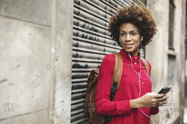 Smiling young woman hearing music with earphones