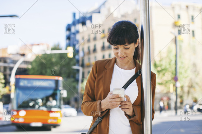 Spain- Barcelona- businesswoman with smartphone waiting at the bus stop