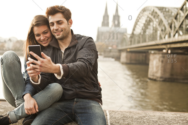 Germany- Cologne- young couple taking selfie in front of Cologne Cathedral