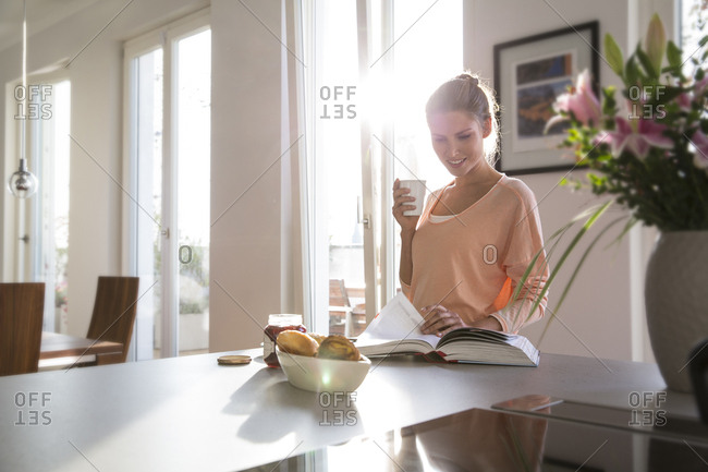Young woman in kitchen having breakfast in kitchen- paging through book