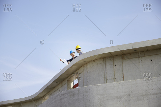 Two men on construction site discussing construction plan