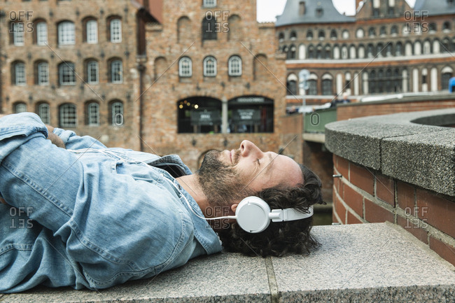 Germany- Luebeck- man with headphones relaxing in the city