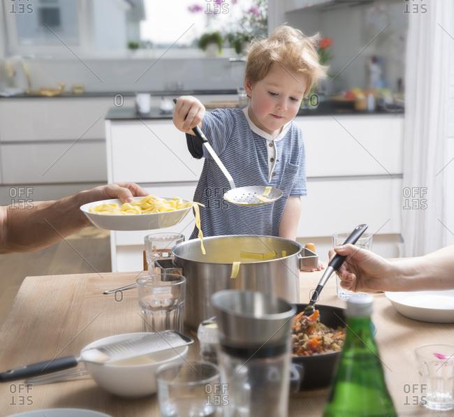 Proud little boy serving pasta in kitchen