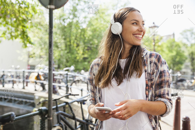 Netherlands- Amsterdam- happy young woman with headphones