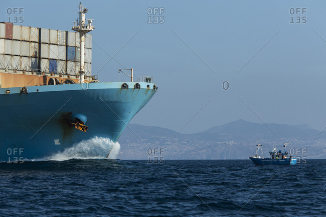 Spain- Andalusia- Tarifa- Container ship and fishing boat