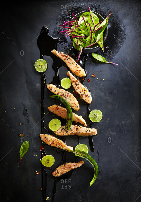 Food art- fried salmon- lime- black sesame- chard- red chili and green chili pepper