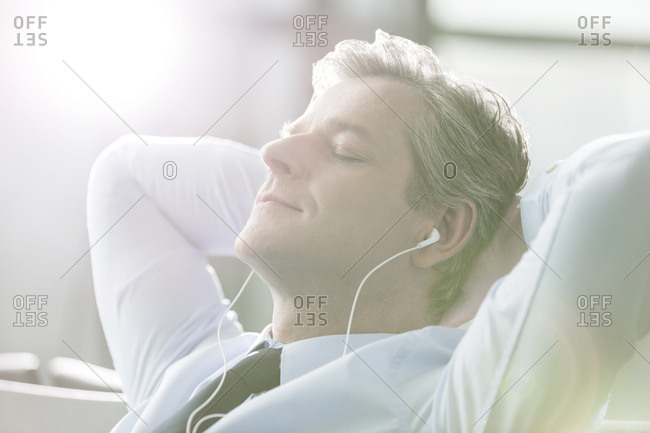 Relaxed businessman with ear buds