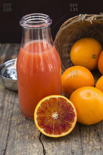 Half and whole blood oranges- bottle of blood orange juice and pocket knife on wooden table