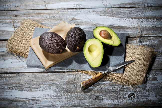 Sliced and whole avocados (Persea americana)- baking paper- knife and slate on jute and wooden table