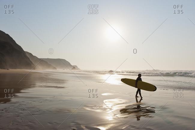Portugal- Surfer walking on beach