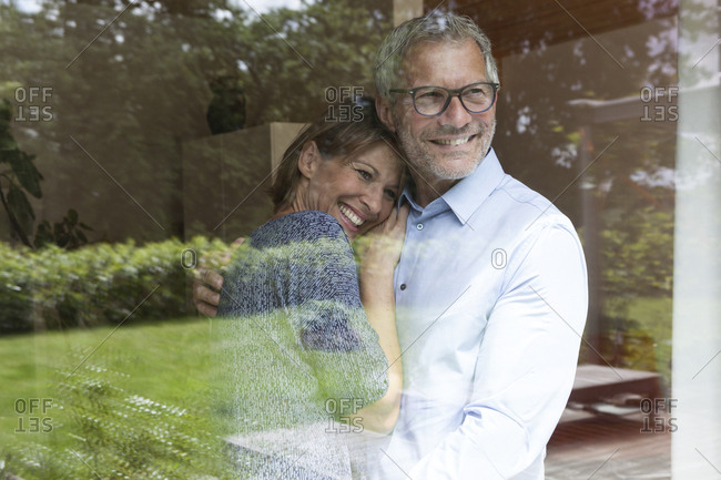 Happy mature couple looking out of window