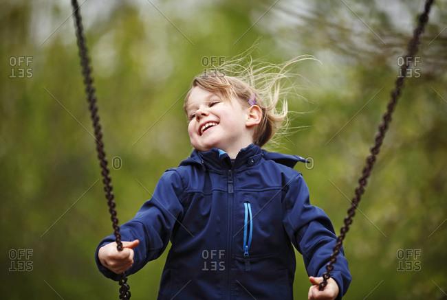 Germany- Baden Wuerttemberg- Girl swinging on swing